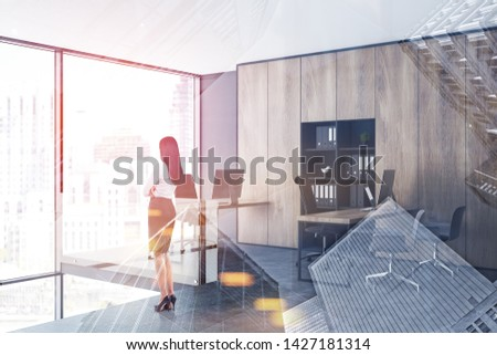 Rear view of businesswoman with black hair standing in panoramic office with gray walls, wooden bookcases and tables. Toned image double exposure #1427181314