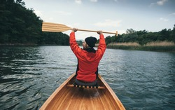 Rear view of canoeist in red jacket holding oars high. Man paddling canoe on cloudy day