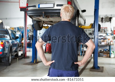 Rear view of car repairer looking at car in auto repair shop with hands on waist