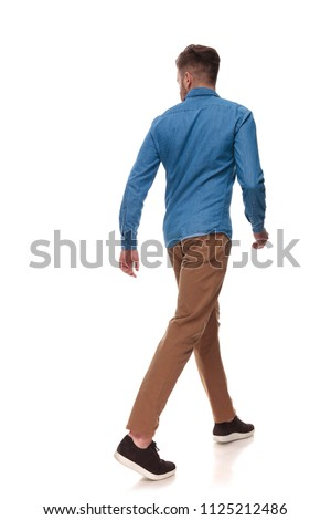 rear view of casual man walking and looking to side on white background, full length picture #1125212486
