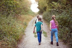 Rear View Of Children On Outdoor Activity Camping Trip Walking Along Countryside Path