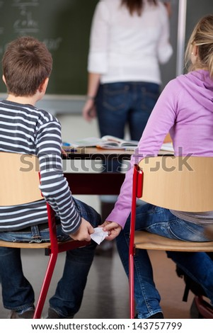 Rear view of children passing cheat in examination with teacher in background at classroom