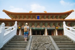 rear view of Chinese woman looking at the old traditional temple in China Asia summer travel. Beautiful asian girl tourist happy lifestyle.