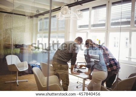 Rear view of colleagues discussing in meeting room at creative office