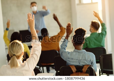 Rear view of college students raising hands to answer teacher's question during a lecture.