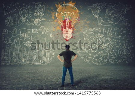 Rear view of confident young man, hands on hips, stands in front of a wall with drawn colorful light bulb and business sketches. Uniqueness of the idea and genius concept.