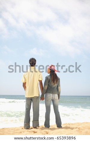 Rear view of couple holding hands at beach - stock photo