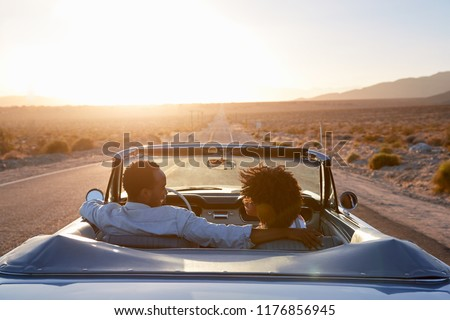 Rear View Of Couple On Road Trip Driving Classic Convertible Car Towards Sunset #1176856945