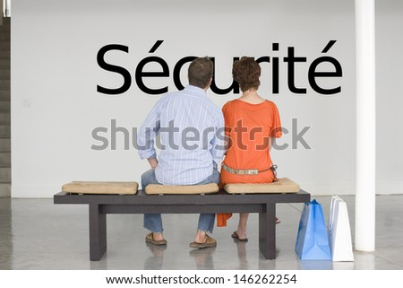 Rear view of couple reading French text 's_curit_' (security) and contemplating about security Photo stock ©