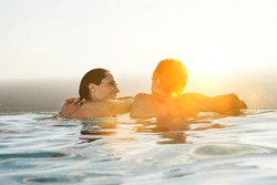 Rear view of couple relaxing in infinity pool at resort