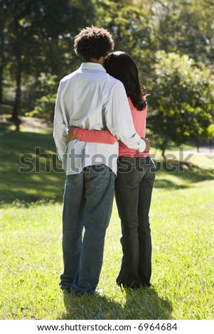 Rear view of couple standing in park with arms around eachother. - stock photo