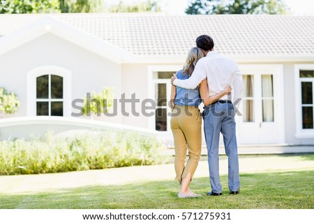 Rear view of couple standing with arm around outside the house