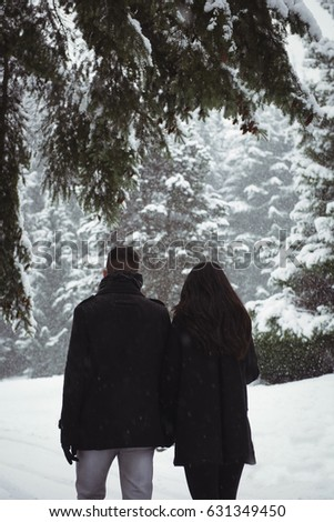 Rear view of couple walking in snowy forest #631349450