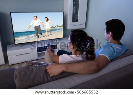 Rear View Of Couple Watching Movie On Television Together In Living Room