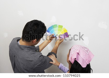 Rear view of couple with color samples to paint their new apartment