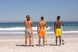 Rear view of diverse male friends standing with surfboard on the beach