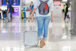 Rear view of elegant professional woman walking in the Air port terminal dragging  luggage suitcase on wheels, indoors. Tourist holiday with  bag in Air port terminal interior, lifestyle.