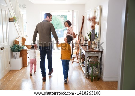 Photo of  Rear View Of Family Leaving Home On Trip Out With Excited Children