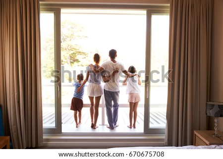 Rear View Of Family On Balcony Looking Out On New Day