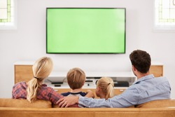 Rear View Of Family Sitting On Sofa In Lounge Watching Television