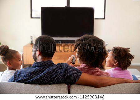 Rear View Of Family With Children Sitting On Sofa Watching TV Together
