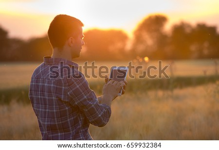 Rear view of farmer in plaid shirt holding tablet on field at sunset in summer