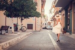 Rear view of fashion tourist woman in hat walking on the city street. Summer wanderlust. Crete, Greece (soft focus)