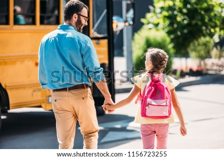 rear view of father and little daughter holding hands and walking to school bus