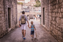 Rear view of father and son holding hands while walking together through small street in old town.