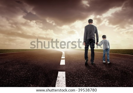 rear view of father and son walking on a street at sunset - stock photo