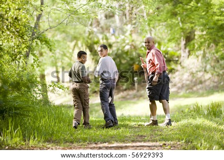 Rear view of father and two sons hiking on trail in woods, 10 and 14 years old
