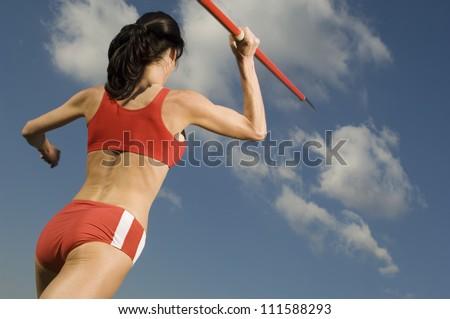 Rear view of female athlete in sportswear throwing javelin