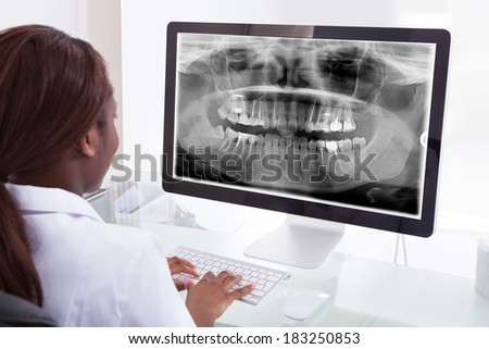 Rear view of female dentist examining jaw Xray on computer in clinic