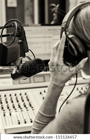 Rear view of female dj working in front of a microphone on the radio. Black and white