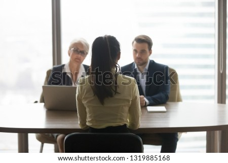 Rear view of female job applicant talking to recruiters listen at job interview, woman vacancy candidate seeker sits back making first impression on hr managers in office, hiring recruitment concept