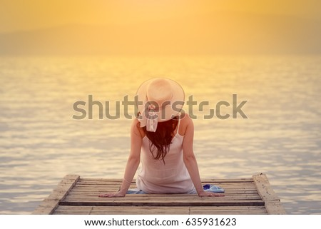 Rear view of female sitting on jetty by the sea at sunset. Summertime concept.    #635931623