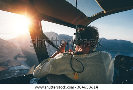 Rear view of female tourist on helicopter tour taking pictures while flying over mountains on a sunny day.