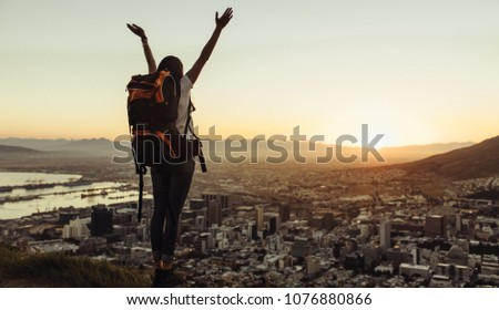 Rear view of female traveler with raised hands standing on the top of a hill and looking at the city with sunset sky. Woman with backpack enjoying the city view from top of a mountain. #1076880866