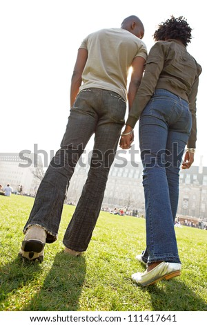 Rear view of figures of a man and woman holding hands while walking through London city on a sunny day.