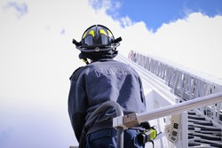 Rear view of firefighter wearing helmet operating firetruck ladder against cloudy blue sky.