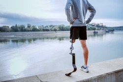 Rear view of fit healthy Caucasian handicapped man in sportswear and with artificial leg standing on quay with hands on hips.
