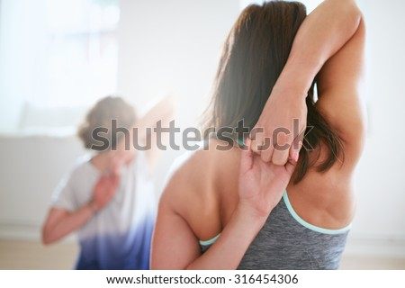 Rear view of fit woman doing gomukhasana in yoga class. Fitness female holding hands behind their back and stretching. Triceps and shoulders workout.