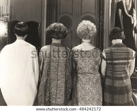 Rear view of four women standing in a row