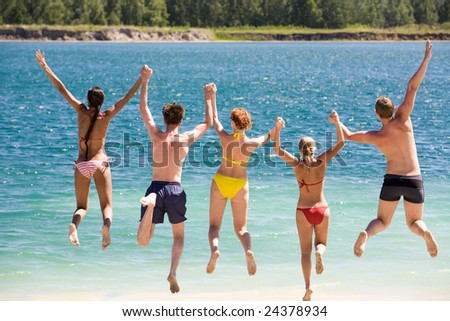 Rear view of friends holding by hands and jumping into water