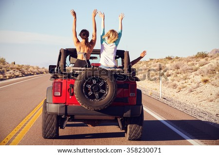Rear View Of Friends On Road Trip Driving In Convertible Car