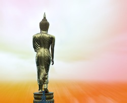 Rear view of golden Buddha statue on blurry pastel color background with copy space.