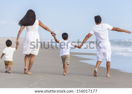 Rear view of happy family of mother, father and two children, boy sons, walking holding hands and having fun in the sand on a sunny beach