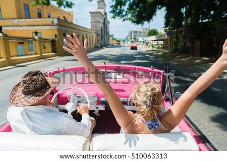 Rear view of happy friends enjoying in the convertible car drive through Havana