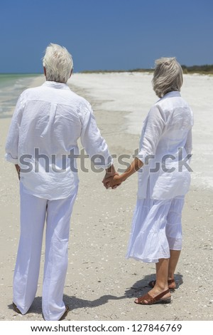 Rear view of happy senior man and woman couple holding hands together looking out to sea on a deserted tropical beach with bright clear blue sky.