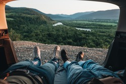 Rear View of Happy Young Couple Lying in Trunk of Their Car and Enjoying Roadtrip, Mountains and River on the Horizon